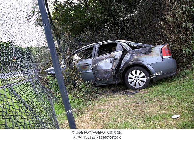 burned out stolen car crashed into a chain link fence in the uk