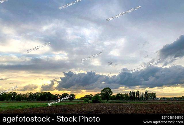 Colorful countryside sunrise or sunset over the agraric farmfields showing the dramatic colors and stormy clouds in the dark sky