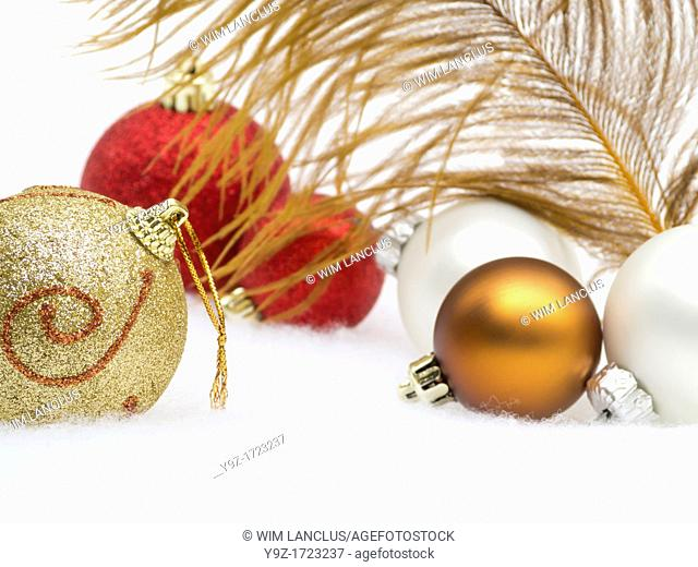 Christmas decoration from baubles and feather in snow