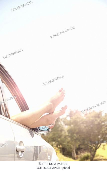 Young womans bare feet resting on car window