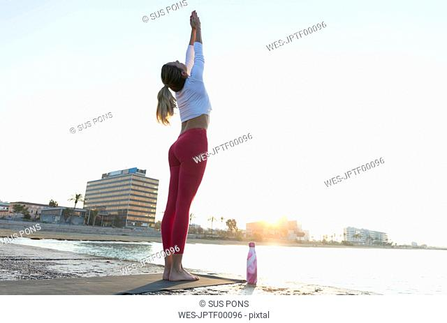Young woman practicing yoga on the beach, doing sun salutations