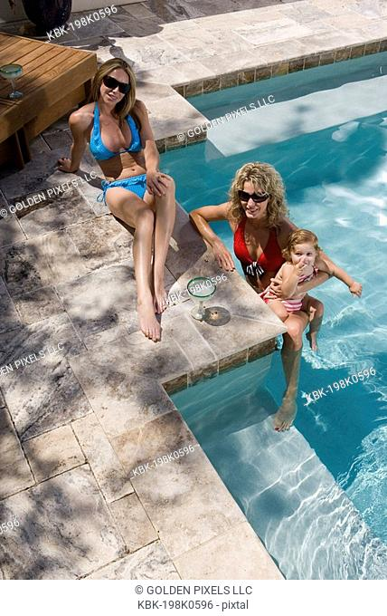 Two young women and baby at the side of a swimming pool