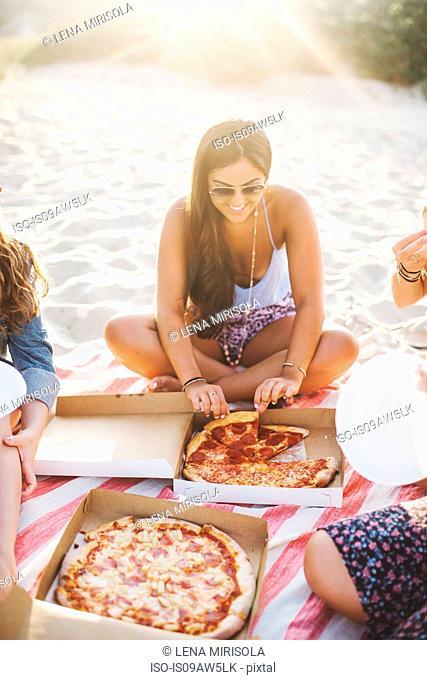 Women sitting on beach sharing a pizza