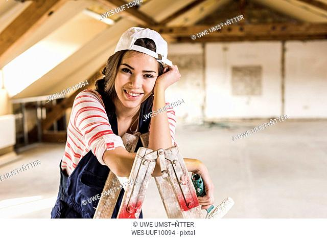 Young woman renovating her new home, holding paint roller