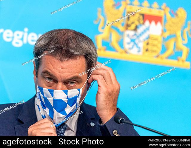 13 August 2020, Bavaria, Munich: Markus Söder (CSU), Minister President of Bavaria, puts on his face mask after a press conference on the latest developments at...