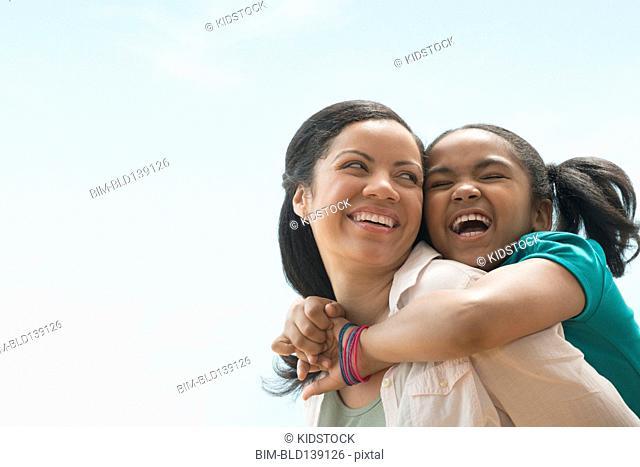 Mixed race mother carrying daughter piggyback outdoors