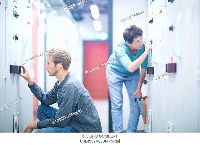 Male and female technicians turning switches in technical room