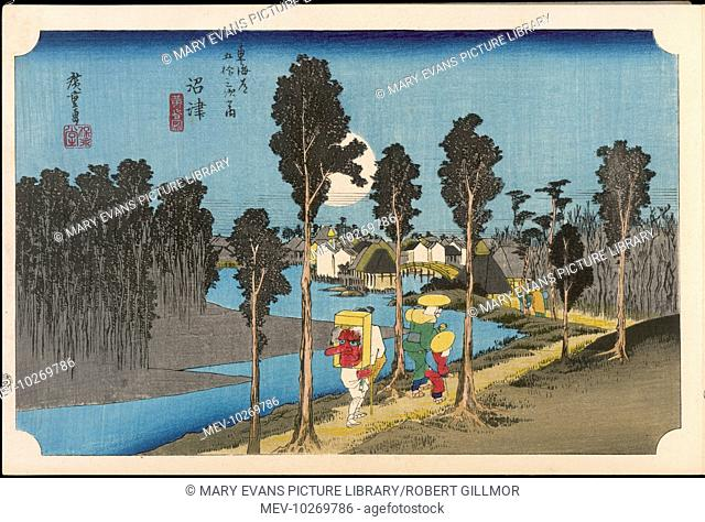 13 Namazu - Travellers walking along the river bank, lined with trees, towards the village ahead, under a huge full moon in a deep blue sky