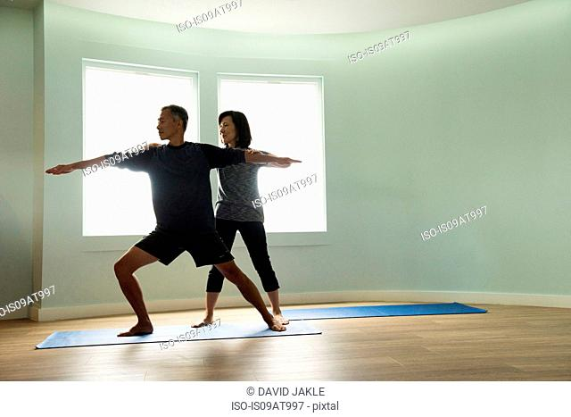 Front view of mature couple doing yoga together, correcting warrior pose