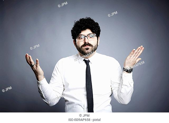 Portrait of young man, hands open in questioning expression