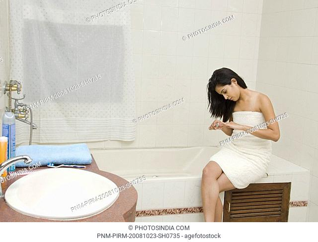 Woman filing nails in the bathroom, Gurgaon, Haryana, India