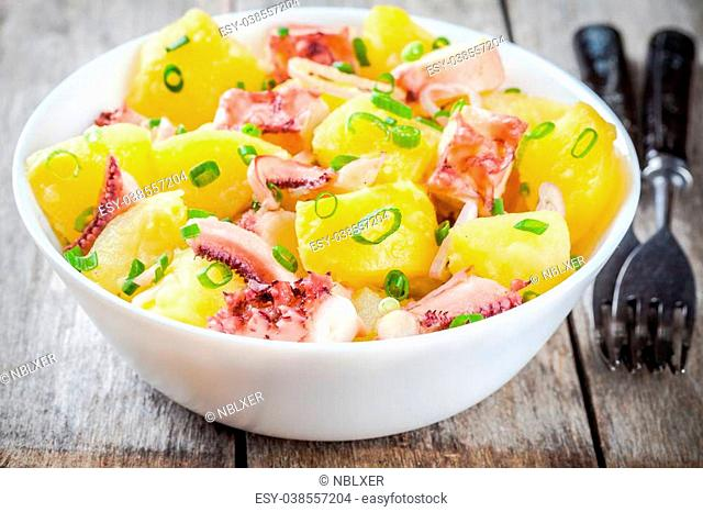 Italian food: salad with octopus, potatoes and onions on rustic background
