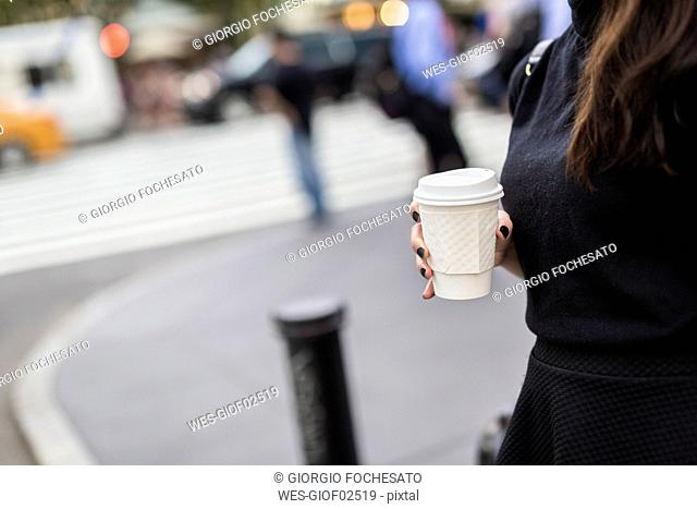 Woman with coffee to go the street, partial view