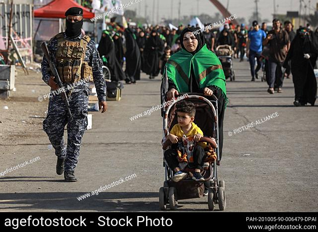 05 October 2020, Iraq, Karbala: A member of the Iraqi security forces (L) observes Shia Muslims march from Baghdad to visit the the Husayn Mosque in Karbala on...