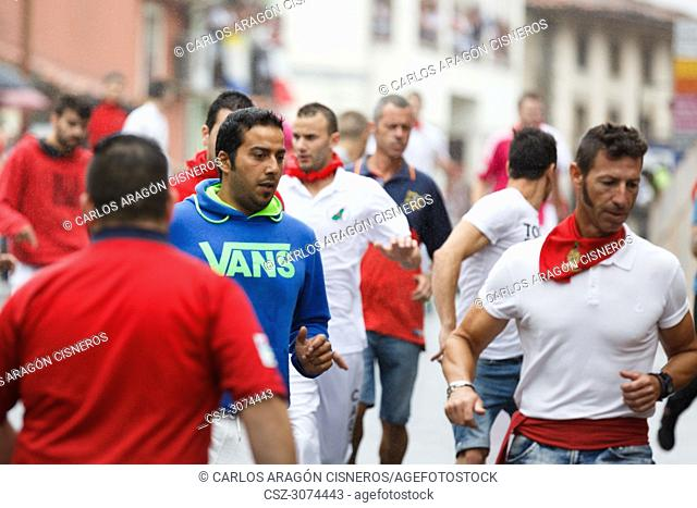 AMPUERO, SPAIN - SEPTEMBER 8: Unidentified group of people in the Bull Run, encierro, on the street during festival in Ampuero, celebrated on September 8