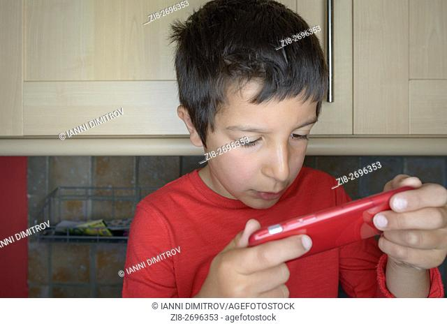 Boy-7 ,plays games on mobile phone