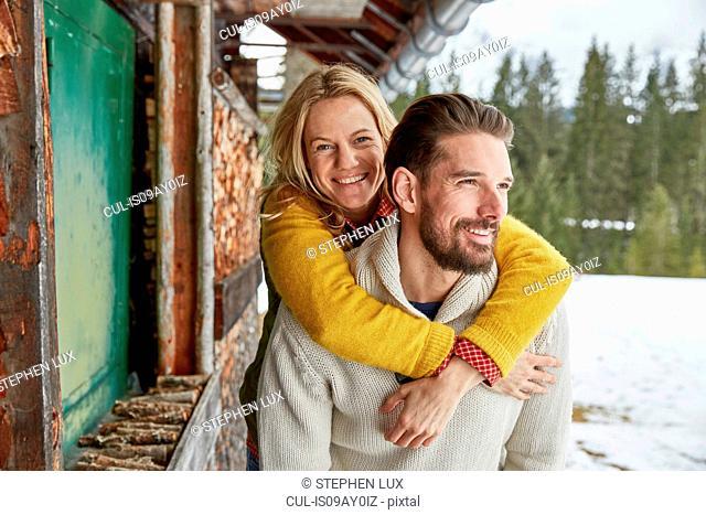 Young man giving piggyback to girlfriend outside log cabin, Elmau, Bavaria, Germany