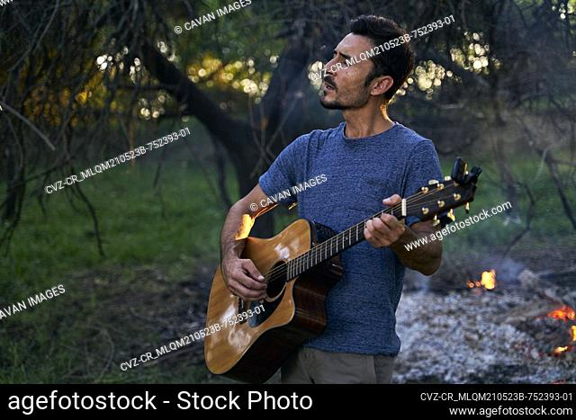 portrait of young musician playing guitar at sunset