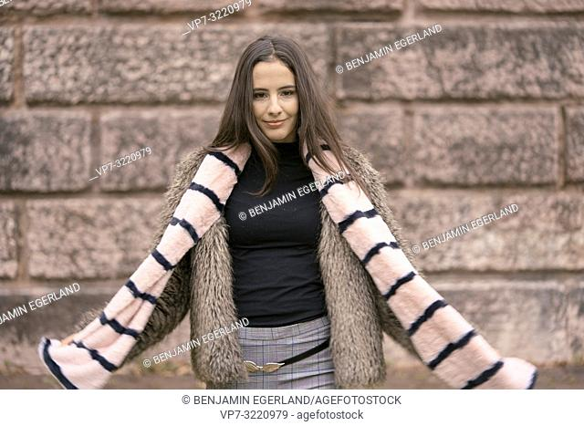 playful woman with scarf, fashionable clothes, in Munich, Germany