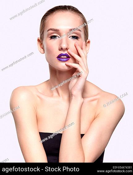 Beauty portrait of young woman with violet lips makeup. Female with hand near face on gray background