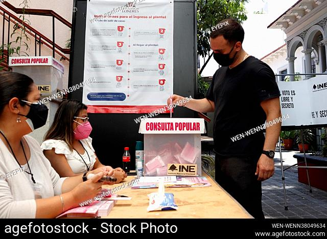 A person puts their vote inside of the ballot box, during the '2021 Popular Consultation' with reason to consult citizens if the former Presidents of Mexico are...