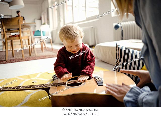 Baby boy exploring a guitar with his mother