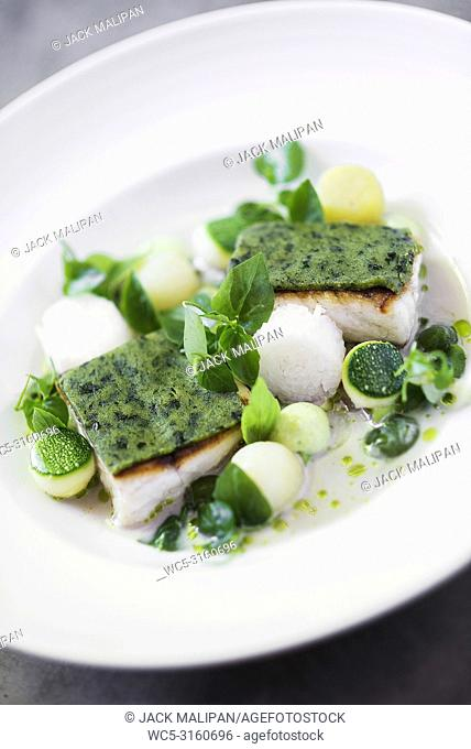 gourmet fish fillet with herbs vegetables and citrus cream sauce
