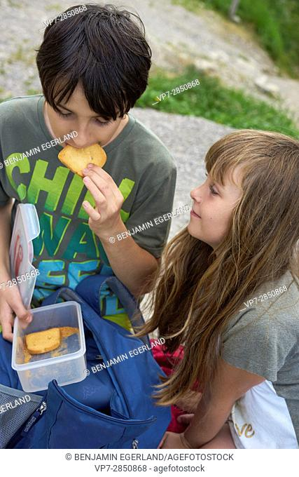Boy nejoys eating rusk while taking rest with female friend