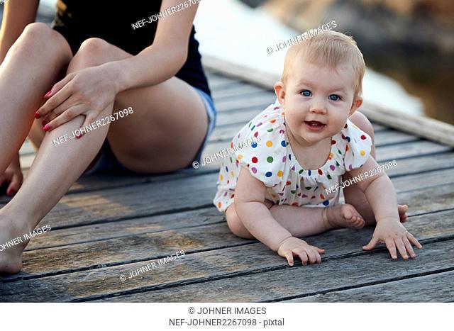 Portrait of baby girl sitting on pier