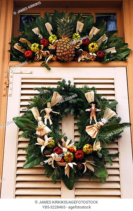 A Christmas wreath with fruit and natural ingredients adorns a door in Williamsburg, Virginia