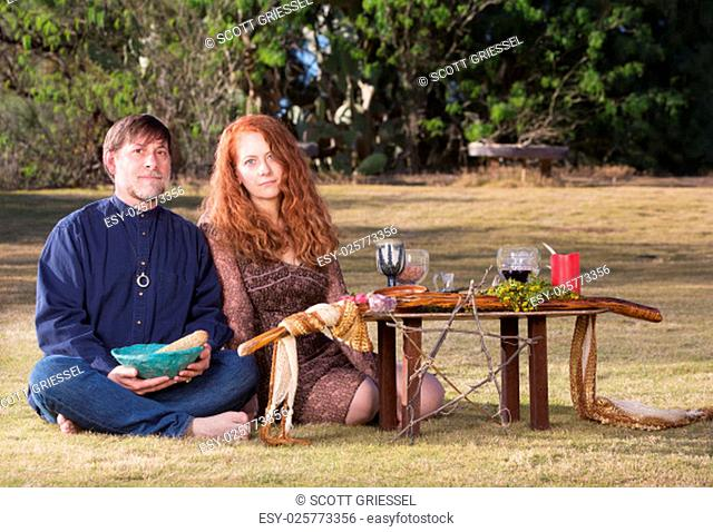 Caucasian pagans sitting with smudge stick at outdoor altar