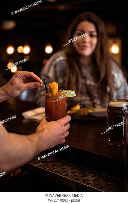 Bartender holding cocktail at bar counter