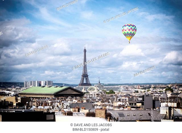 Hot air balloon floating over cityscape, Paris, France