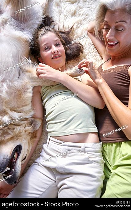 Mother and daughter lying on the floor by their golden retriever dog