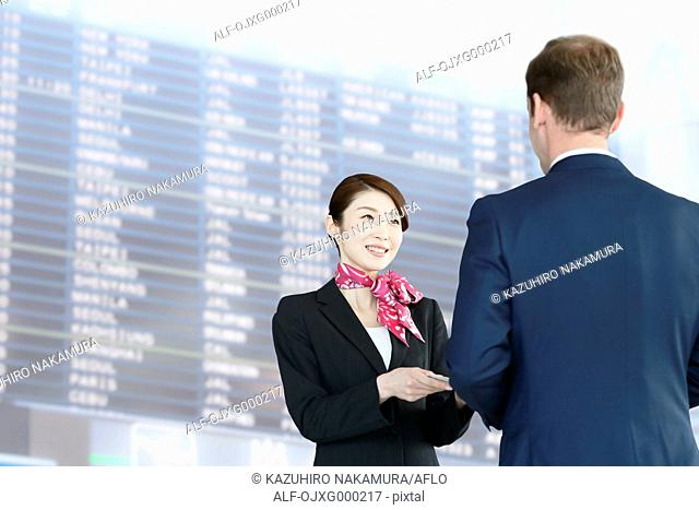 Japanese attractive flight attendant helping customer at the airport