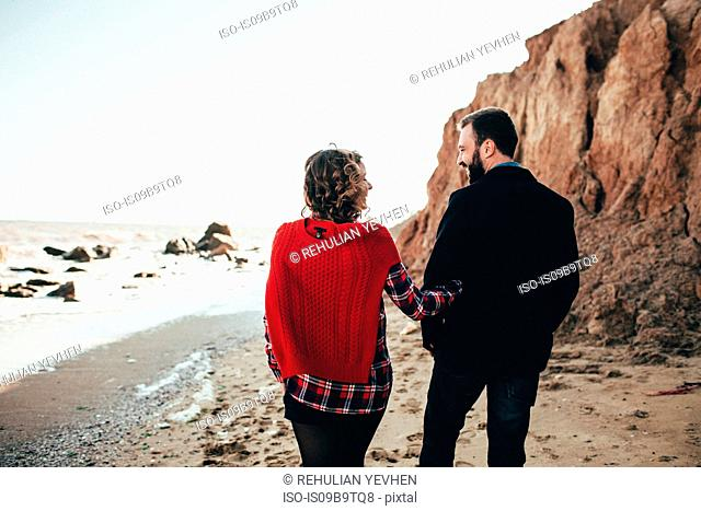 Rear view of romantic mid adult couple strolling on beach, Odessa Oblast, Ukraine