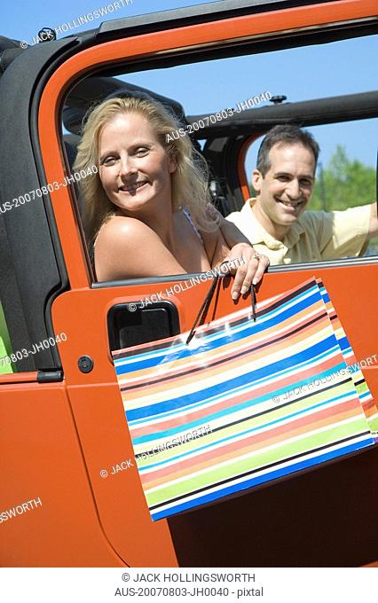 Mature woman sitting with a man in a car and smiling