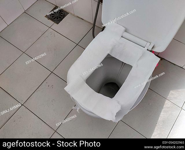Toilet paper put on Open Toilet seat. Cover The Toilet Seat With Tissue Paper. Public toilet
