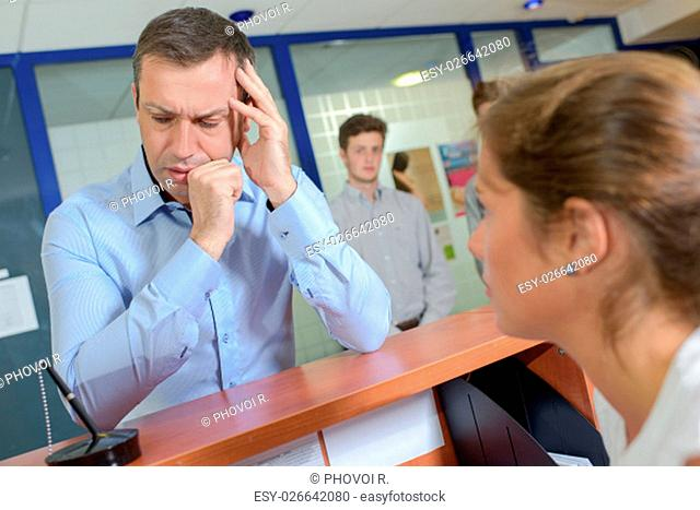 Man at reception desk, in pain