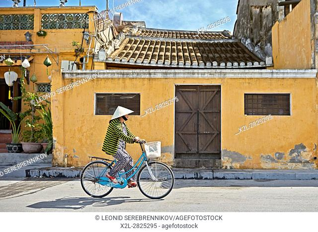 Woman on bicycle in Hoi An Ancient Town. Quang Nam Province, Vietnam