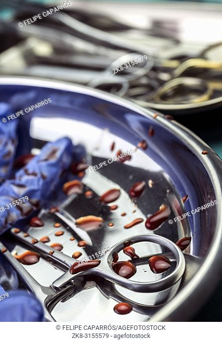 Gloves blue and scissors stained with blood on a tray in an operating theater, conceptual image