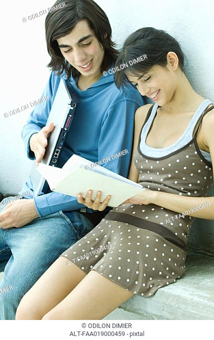 Young friends reading book together