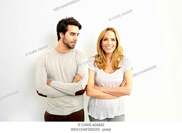 Portrait of smiling woman standing besides young man watching her in front of white background