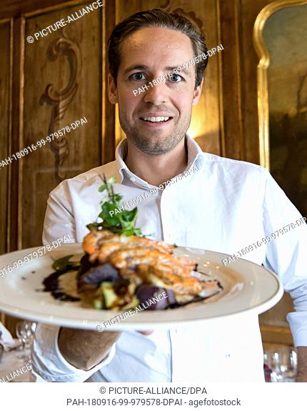 14 September 2018, Bavaria, Langenpreising: Fabian Riedel, Managing Director of Crusta Nova, holds a plate with a prawn skewer (Pacific White Shrimp) in his...