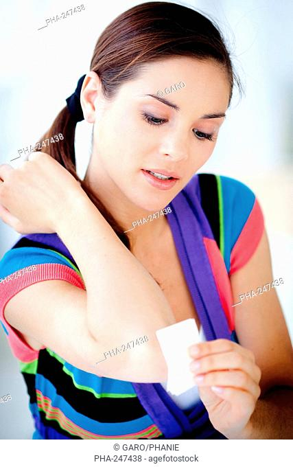 Woman applying gauze compress on her elbow