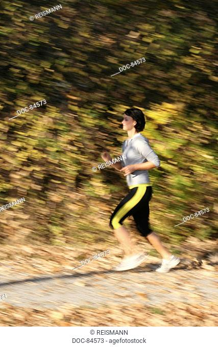 Young Woman running on a sunny autumn afternoon