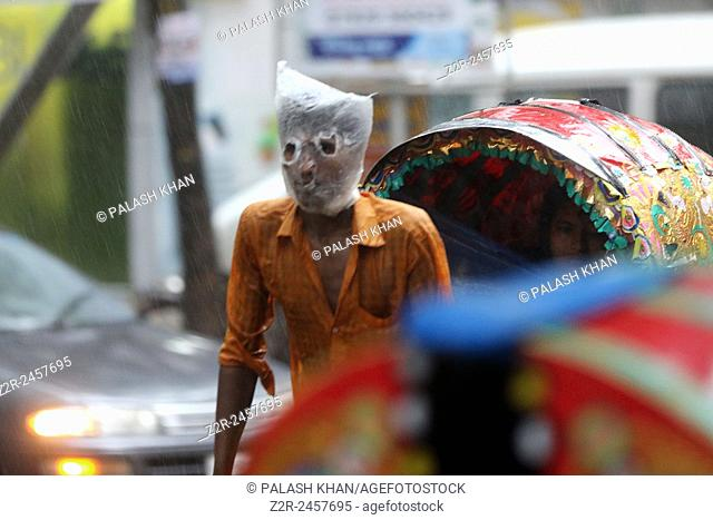 Rickshaw puller wears a plastic bag on his head and face as he carries passengers in a rain-soaked street of Dhaka, Bangladesh, 13 June 2015