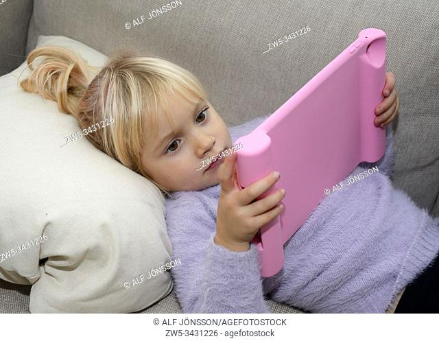 Little blond girl, 3 1/2 years old, looking at a tablet computer in Ystad, Scania, Sweden