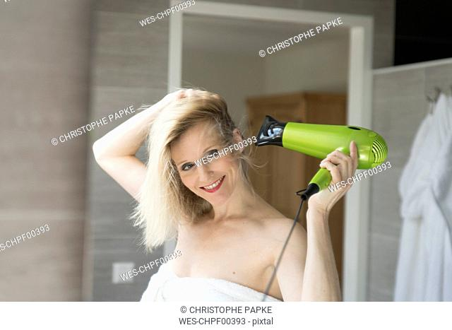 Portrait of smiling blond woman using hair dryer in the bathroom