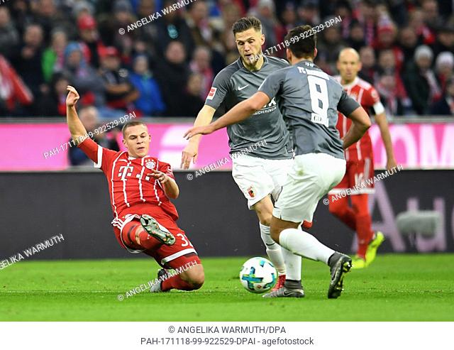 Munich's Joshua Kimmich (L-R) and Augsburg's Jeffrey Gouweleeuw and Rani Khedira vie for the ball during the Bundesliga soccer match between Bayern Munich and...